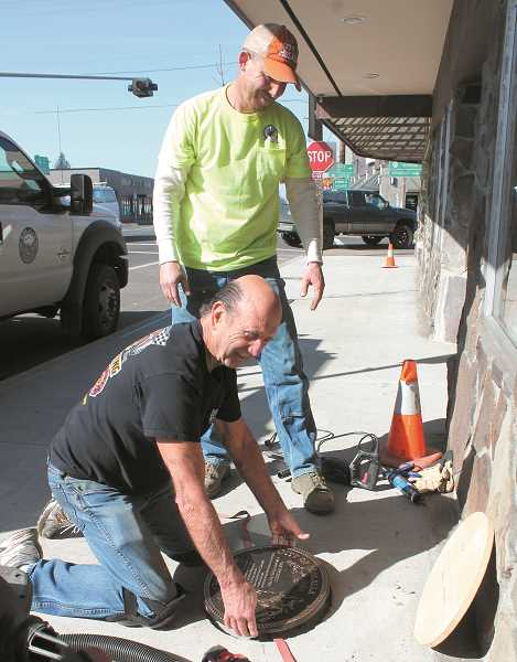 PEGGY SAVAGE - Jim Taylor, a TEAM Molalla board member, setting a Rodeo Walk of Fame plaque  in a Main Street sidewalk last year with help from a city employee.