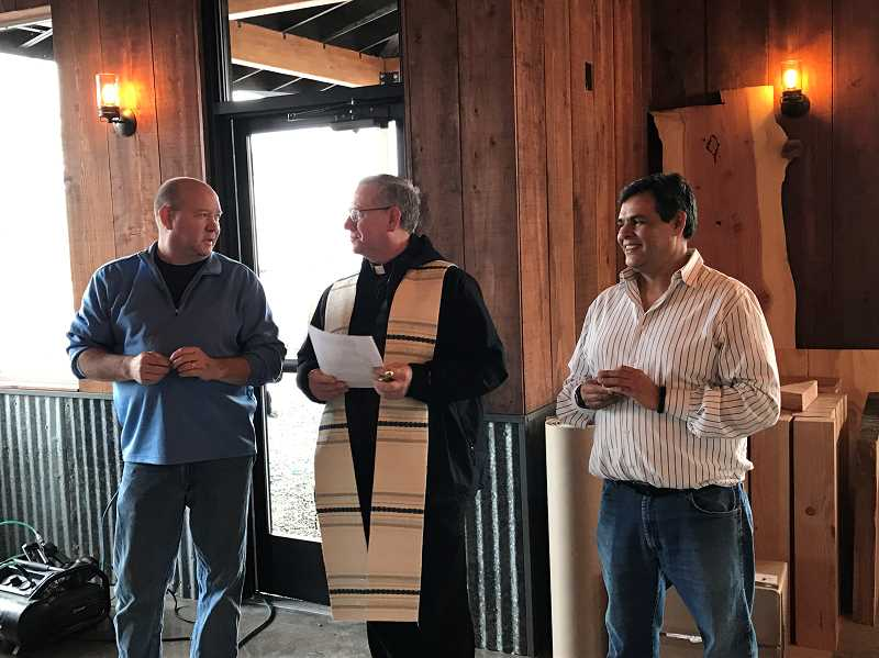 TYLER NIZER - Markum Inn owner Mark Burnett, Father Philip Waibel, OSB, pastor of St. Mary Church in Mount Angel, and General Manager Julio Valera are ready for the blessing of the building.