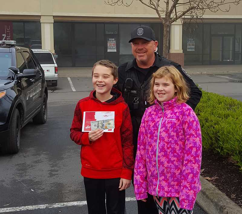MPD - Two happy kids who had been riding in a car with their dad show off the $100 Secret Santa bill this Molalla Police officer had just given them after pulling over the car. The Secret Santa funds are donated by Molalla citizens who want to share some Christmas Joy with fellow Molallans.