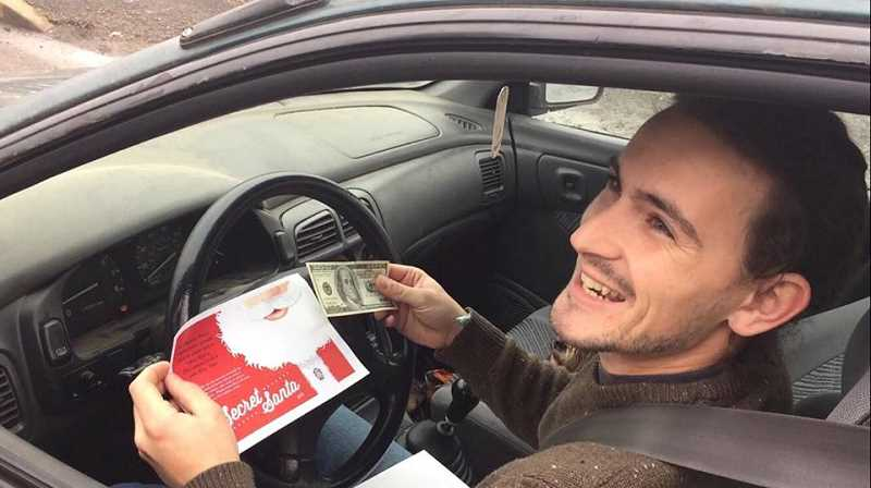 CONNER WILLIAMS - Chief Rod Lucich pulled over a car Wednesday afternoon driven by a young man home from college for the holidays. He is all smiles when he pulls the $100 bill out of the Secret Santa envelope.