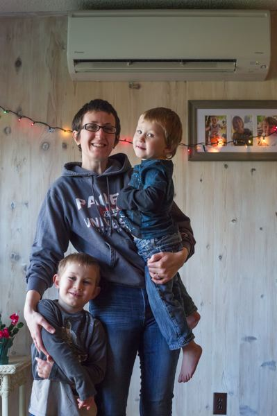 PAMPLIN MEDIA GROUP: JONATHAN HOUSE - Giselle Northy and her children, Eric, left, and Isaac in front of their new ductless heat pump system. Constantly feeding a woodstove was getting old and leaving her house cold at times, she says.