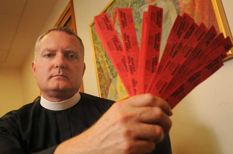 REVIEW PHOTO: VERN UYETAKE - The Rev. Jeremy Lucas of Christ Church Episcopal Parish in Lake Oswego holds the 150 tickets he purchased in an all-star softball team's raffle. When Lucas won in July, he vowed to transform his prize -- an AR-15 rifle -- into artwork.