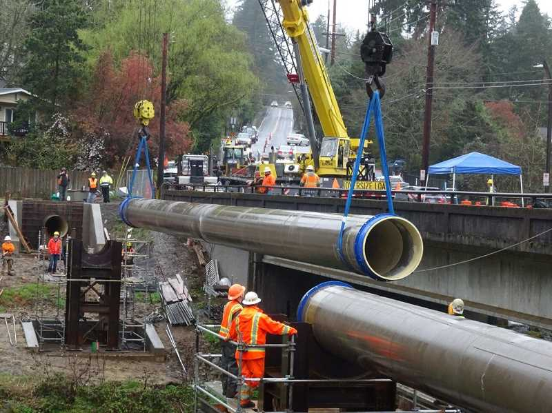 SUBMITTED PHOTO: LAKE OSWEGO-TIGARD WATER PARTNERSHIP - Construction crews lower a segment of pipe into place over Oswego Creek near the McVey Avenue Bridge in March, completing the last segment of a new 10.5-mile-long pipeline.