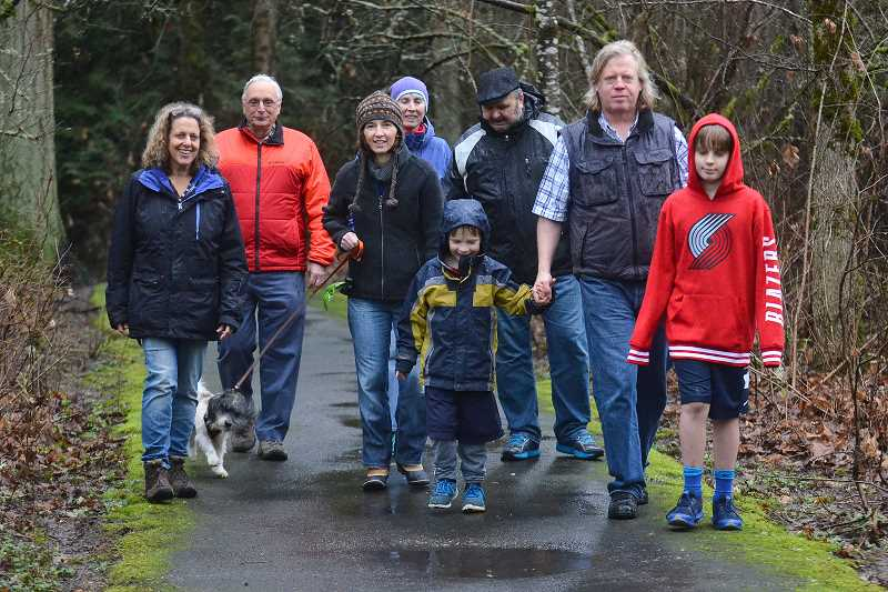 Hallinan neighbors (from left) Christy Clark, David Hastings, Celine Mattersdorff, Barbara Fisher, Don Flowers, Donald Mattersdorff and children Oscar and Lachlan walk along the main trail through Hallinan Woods. The group, along with other neighbors, are urging the City to expand the park by purchasing adjacent private property.