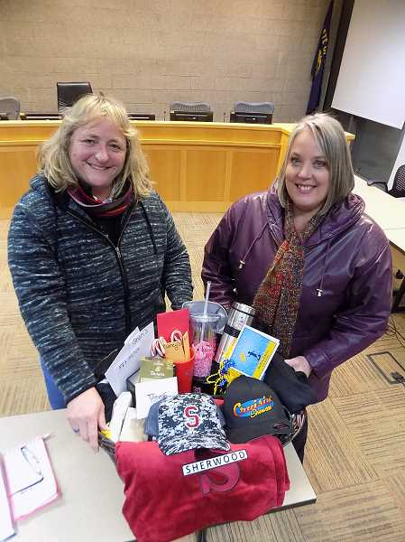 GAZETTE PHOTO: RAY PITZ - Former Sherwood Councilors Linda Henderson and Renee Brouse display a basket of goodies donated by local businesses to wounded Trooper Nic Cederberg who was shot outside of Sherwood on Christmas night.