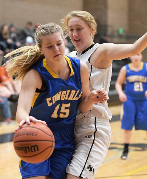 LON AUSTIN/CENTRAL OREGONIAN - Rylee Troutman goes hard to the basket against Amanda Smith, of Sisters. Troutman led all scorers in the game with 16 points.
