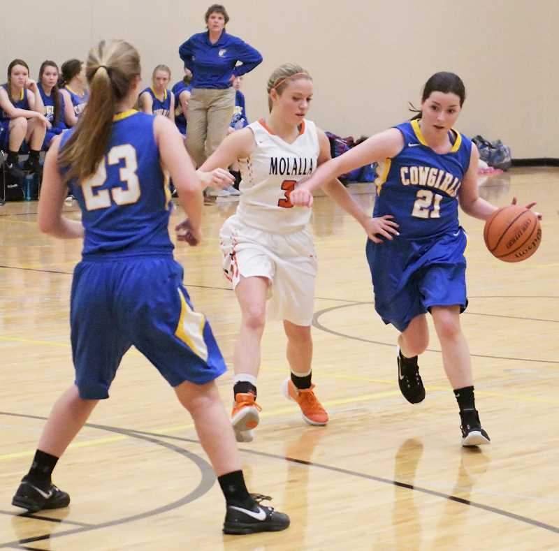 LON AUSTIN/CENTRAL OREGONIAN - Sarah Connolly drives around Molalla defender Sierra Cox, while Page Kump (23) sets a screen. Molalla easily won the game.