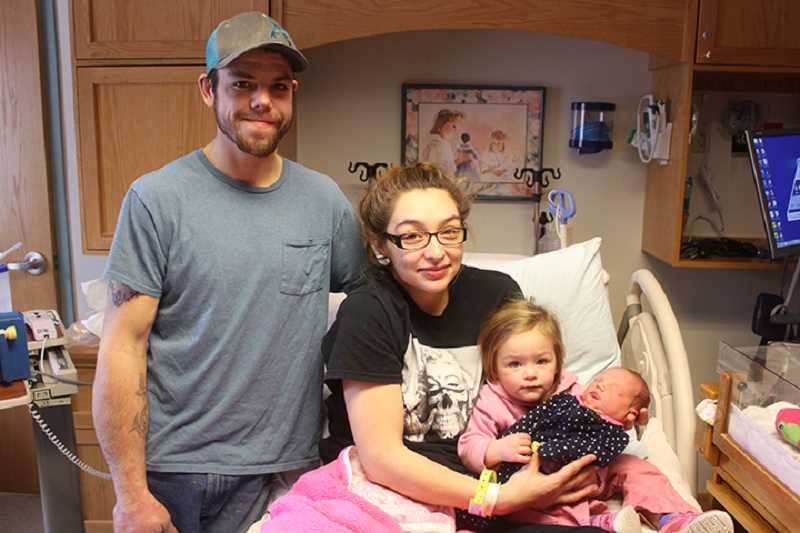 SUSAN MATHENY/MADRAS PIONEER - Newborn RaeLynn Henderson sleeps through her photograph with parents Johnny Henderson and Bailey Roberts, and sisterMariah, 1, at St. Charles Madras.