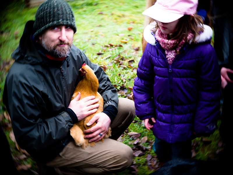 CONTRIBUTED PHOTO: JOEL VAUGHN - 'Aharown Luke introduces a chicken to a guest at his farm during a tour on Saturday, Dec. 31.