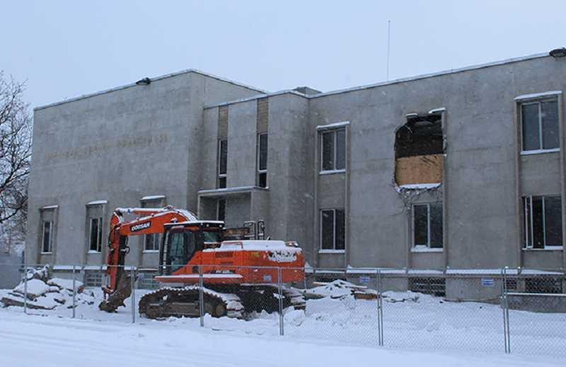 HOLLY M. GILL - The contractor had bashed holes in the front wall and door area of the old courthouse last week, as demolition began on the old Jefferson County Courthouse. Heavy snowfall called a halt to demolition this week.