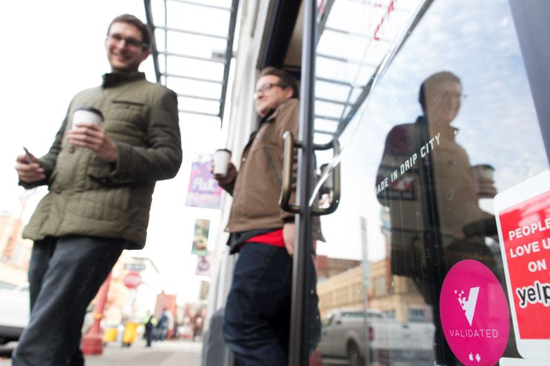 JAIME VALDEZ - Look for the pink sticker: Validated co-founders CTO Alex Wilhelm and CPO Ian Lyman walk out of Deadstock coffee shop in Old Town after purchasing drinks at the business who supports their app business. Spend $5, get $1 credit, or $10 get $2, to be used to pay for transporation.