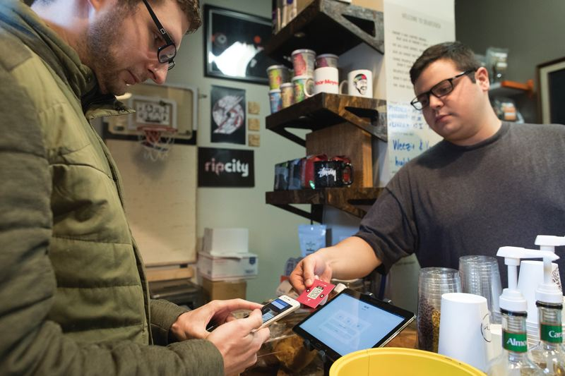 JAIME VALDEZ - Validated CTO Alex Wilhelm buys coffee to trigger more credits at the Deadstock coffee shop in Old Town. The credits can be used against the cost of Lyft, Uber, Biketown or ReachNow and in future, they say, parking meters and TriMet rides.