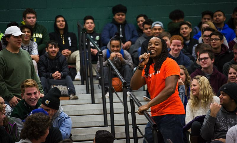 TIMES PHOTO: ADAM WICKHAM - Motivational speaker and rapper Omekongo Dibinga scales the bleachers where Tigard High School students were sitting for an assembly in the gymnasium.