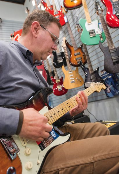 PAMPLIN MEDIA GROUP: JOHN VINCENT - Jason Busch tries out a new Fender Stratocaster in Portland Music Company's Central Eastside Industrial District store. The company stocks hundreds of new guitars, from acoustic instruments to hard-to-find limited edition models, plus amps and Fx pedals.