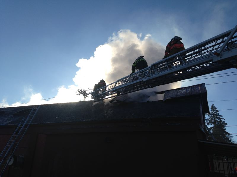 PHOTO COURTESY: CLACKAMAS FIRE - A fire-truck company goes to the roof to ventilate a fire on Molalla Avenue in Oregon City.