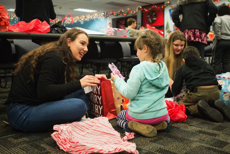 OUTLOOK PHOTO: JOSH KULLA - Wilson High School leadership students Sophie Rubin and Amy Sloan help Transition School students open gifts during a holiday party Friday at the Inverness Jail in North Portland.
