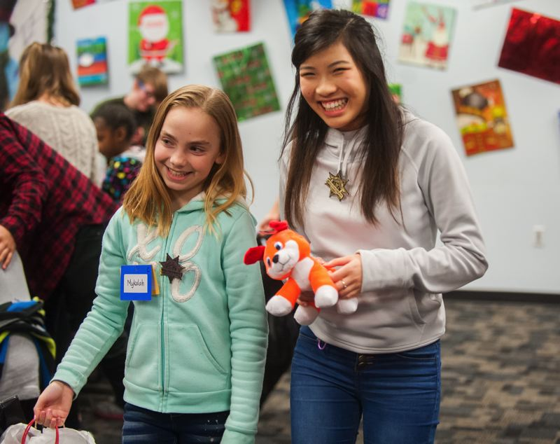 OUTLOOK PHOTO: JOSH KULLA - Mykaylah, a Transition School student, enjoys gifts with Wilson High School student Anna Kien Friday during a holiday party for disadvantaged children held at the Inverness Jail in North Portland.