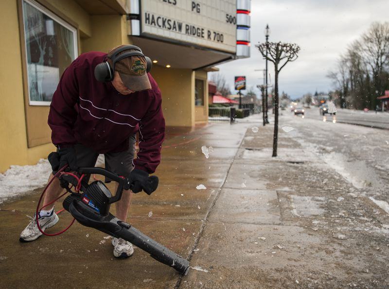 OUTLOOK PHOTO: JOSH KULLA - Mt. Hood Theater employee Michael Metcalf clears ice from the sidewalk along Powell Boulevard Monday as the Portland area started to thaw out from the weekend's ice storm.