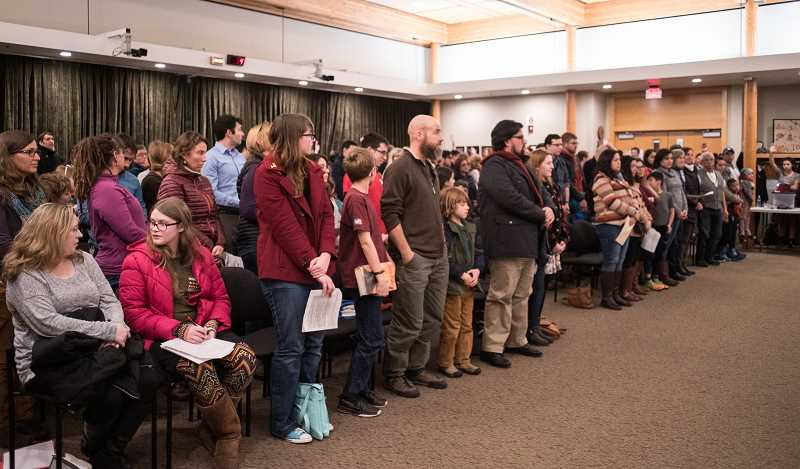 NEWS-TIMES PHOTO: CHASE ALLGOOD - Most of the roughly 150 people in attendance stand or raise their hands in favor of the Sanctuary City designation.