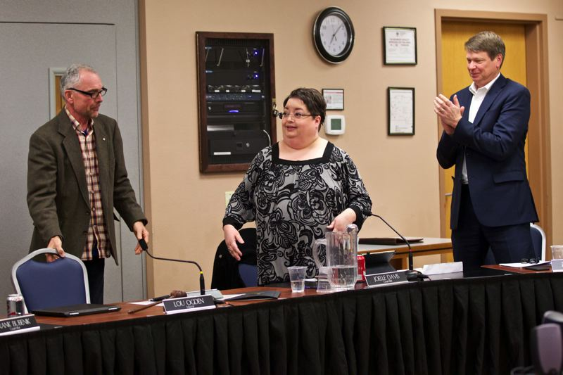 TIMES PHOTO: JAIME VALDEZ - After being unanimously chosen as Tualatin City Council president at Monday's meeting, Joelle Davis, center, stands to change seats. Also pictured: Mayor Lou Ogden, left, and City Councilor Jeff DeHaan, right.