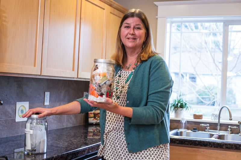 PAMPLIN MEDIA GROUP: JONATHAN HOUSE - Kathy Peterman holds two jars of waste that contains all of her non-recyclable trash consumed in 2016.