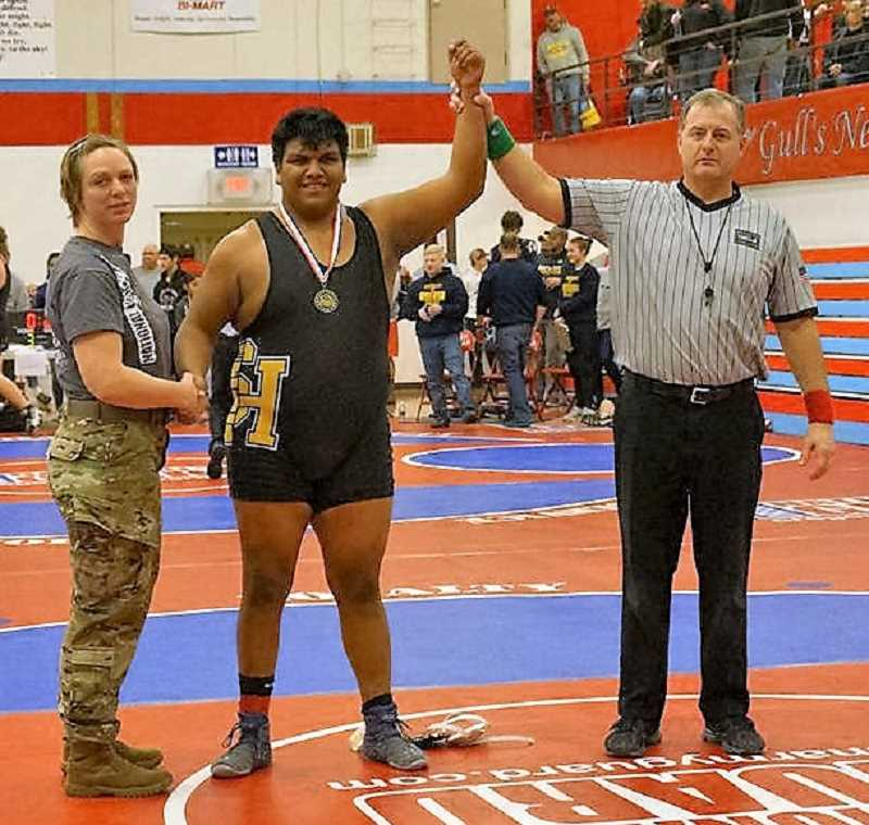 PHOTO CREDIT: BG AGUIRRE - Lions senior Miguel Olmedo, center, pinned Ilwaco (Wash.) junior Marcello Lazaro in 3:18 for the heavyweight championship at the Pacific Rim Armed Forces Tournament in Seaside.