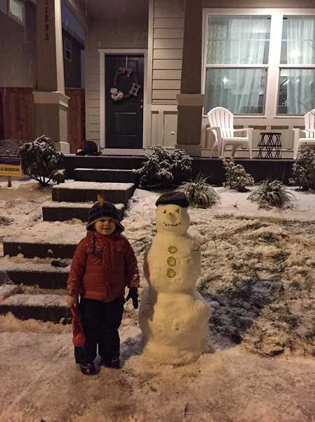 COURTESY OF BROOKE HIGGS  - A youngster poses next to a snowman in Sherwood on Tuesday evening.