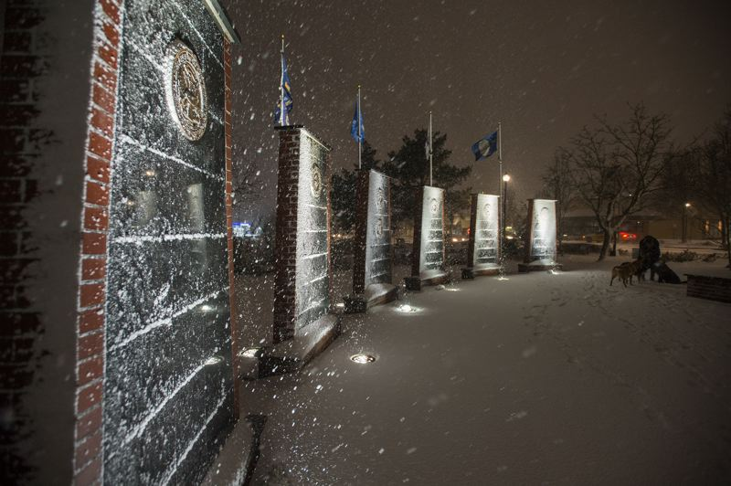 OUTLOOK PHOTO: JOSH KULLA - Gresham's Heroes Memorial still drew visitors last night despite the onset of a big winter storm.