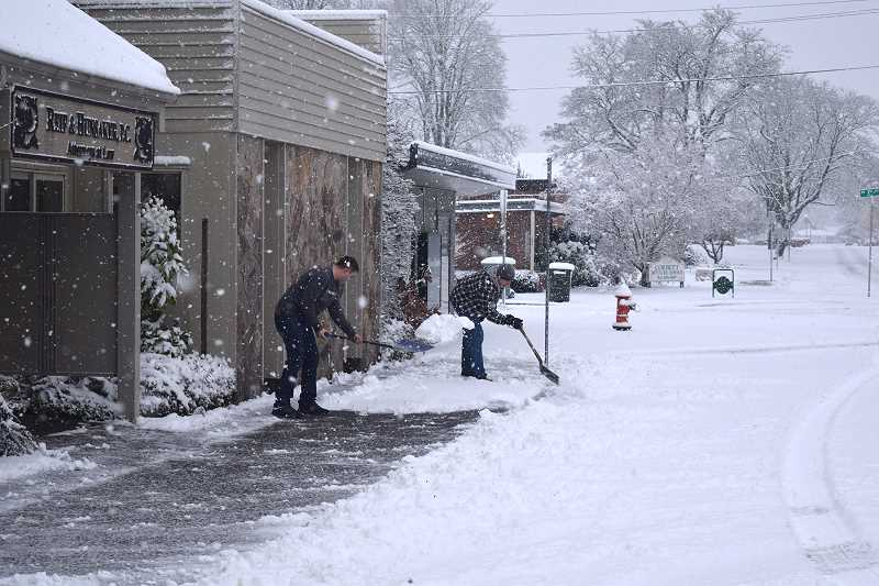 JOHN BAKER - With the snow piling up, a couple hearty souls work to keep the sidewalks clear along Grant Street in downtown Canby.