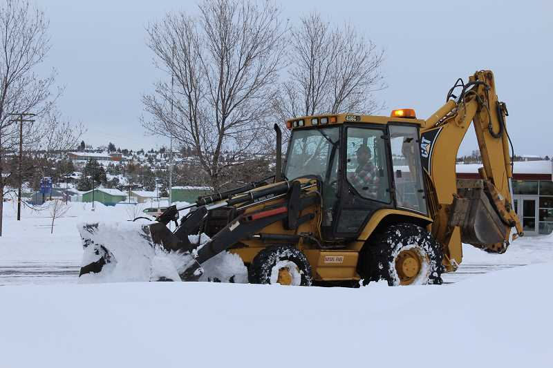 HOLLY M. GILL - A backhoe clears the parking lot at Buff Elementary Monday, after a new batch of snow overnight.