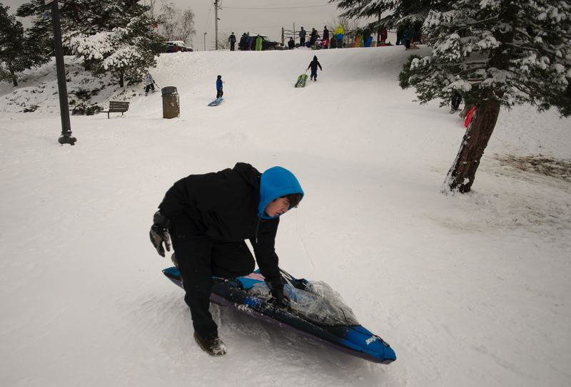 OUTLOOK PHOTO: JOSH KULLA - A sledder prepares to head back up the hill after yet another run in Main City Park today.