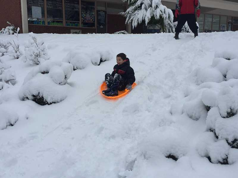 TIDINGS PHOTO: ANDREW KILSTROM - Dylan Hoxha is enjoying his snow day after spending the morning sleeding down small hills at Cedaroak Park Primary.
