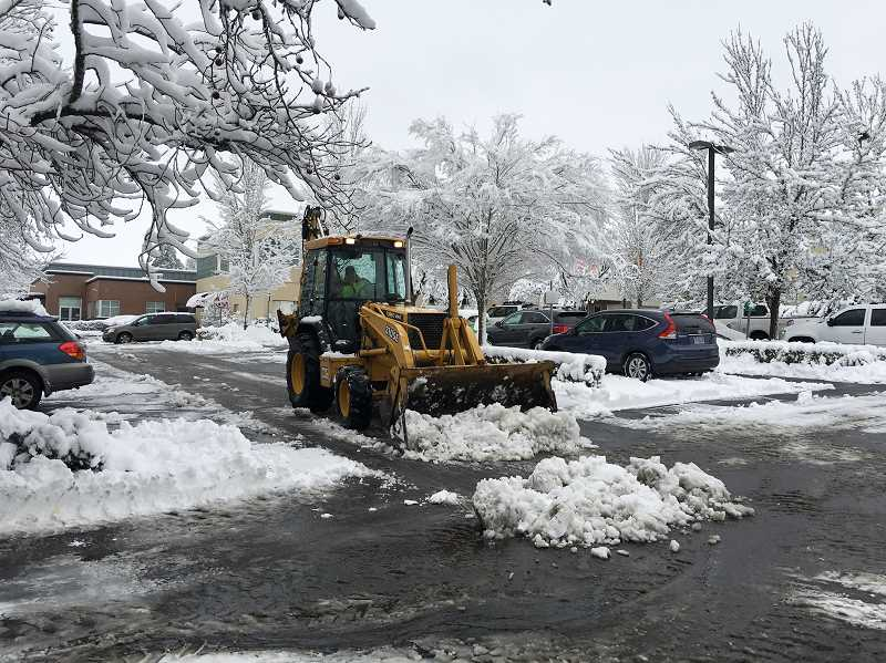NEWS-TIMES PHOTO: JOHN SCHRAG - Workers clear a parking lot in Forest Grove.