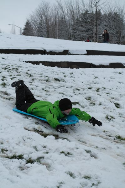 SPOKESMAN PHOTO: CLAIRE GREEN - Children enjoyed the snow day in Memorial Park with sleds and snowboards.