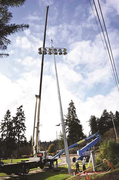 SUBMITTED PHOTO - City workers install one of eight new LED field light poles at George Rogers Park, a project that had to be delayed until an osprey left its nest last fall. The bird's home has since been rebuilt atop one of the poles, and the project is now in the final phase.