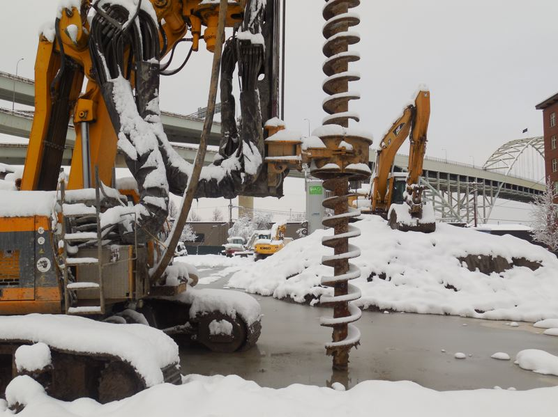 PAMPLIN MEDIA GROUP: JOSEPH GALLIVAN - A snow-covered drill bit sits unused as piling work was delayed by lack of cement. Two workers are visible far right on Thursday at Alliances site at 1411 N.W. Quimby Street.