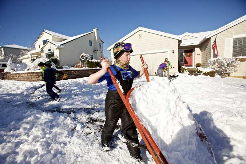 PAMPLIN MEDIA GROUP: JAIME VALDEZ - Aidan Kelly,11, dumps snow from a wheelbarrow as he and his brother, Finn (not pictured) and their neighborhood friends help shovel their Grandpa John Hunter's driveway.
