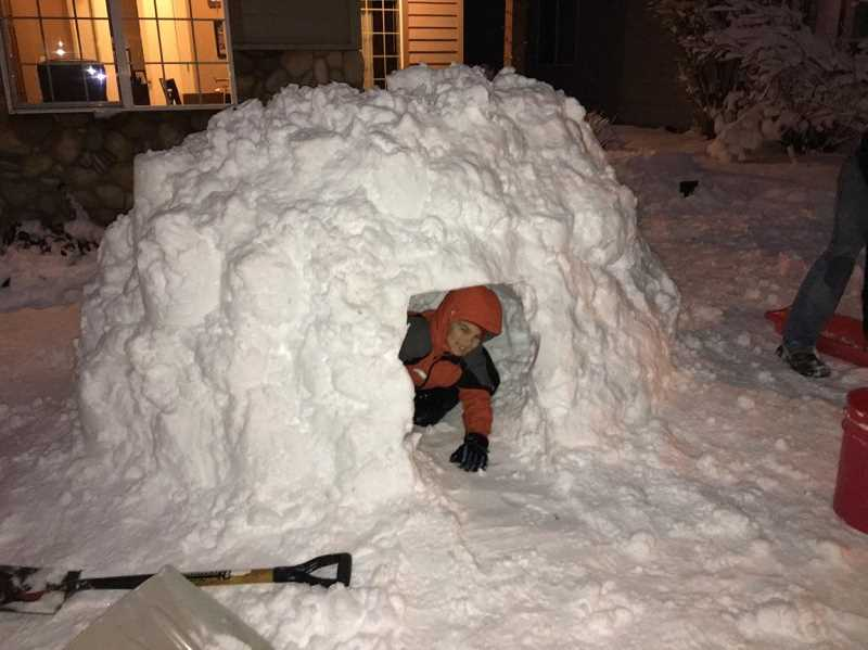 COURTESY OF NICK MANNING - Zachary Manning of Sherwood peeks out of the igloo he built in his front yard on the evening of Jan. 11.