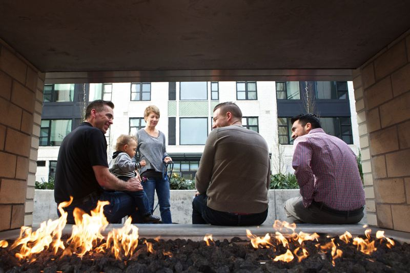 TRIBUNE FILE PHOTO - Bob Ball, holding his son, Parker, left, visits with tenants Lisa Moose, David Carroll and Cristian Gonzales next to an outdoor fireplace in the courtyard of the Northwest apartments.