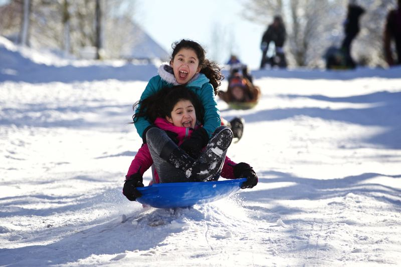 TRIBUNE PHOTO: JAIME VALDEZ - Yasmeen Obeidi, 8, turquoise jacket, and her older sister, Mariam, 10, bounce over a jump on Southwest Fisk Terrace in Sherwood.