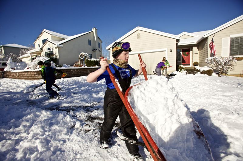 TRIBUNE PHOTO: JAIME VALDEZ - Aidan Kelly, 11, dumps snow as he and his brother, Finn (not pictured), and their neighborhood friends help shovel his grandfather's driveway Thursday, Jan. 12.