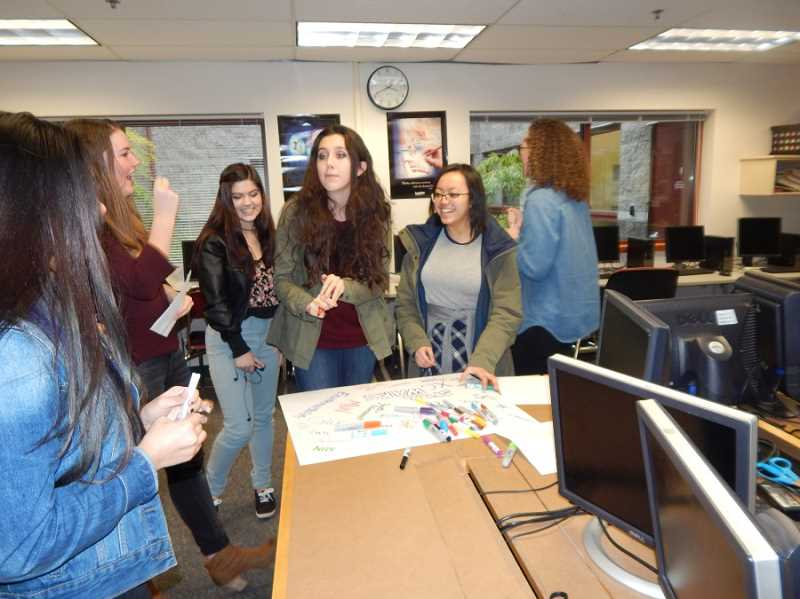 BARBARA SHERMAN - Members of the SHS Girls Who Code group have fun listing their activities on a poster board.