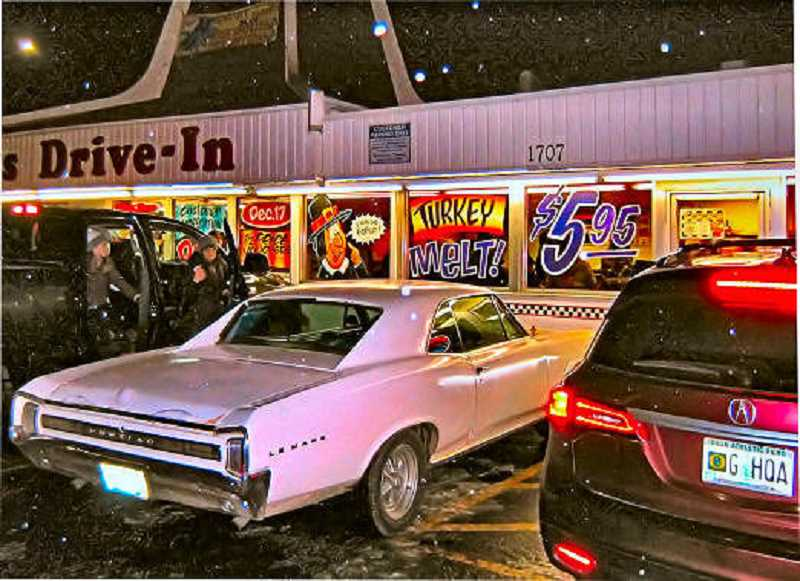 ERIC NORBERG - A few light snow showers fell, spangling this photo with points of light, as customers drove through the parking lot at Mikes Drive In on December 17, often having to drive on through and park across the street, due to the size of the crowd on closing night.