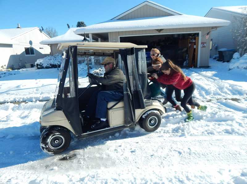 BARBARA SHERMAN - Summerfield resident Ken Toops needed some help from passersby after his golf cart got stuck in snow ruts; they managed to get it turned around and back in his garage.