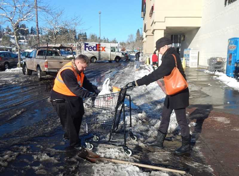 BARBARA SHERMAN - Safeway courtesy clerk Andy Gardner stops shoveling snow to help a customer get her shopping cart across a rough patch of snow.