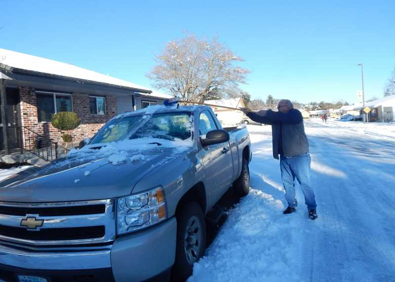 BARBARA SHERMAN - On Jan. 12 King City resident Bryan Rygh uses a broom to get the snow off his truck that had been parked on the street since the snowstorm started Jan. 10.