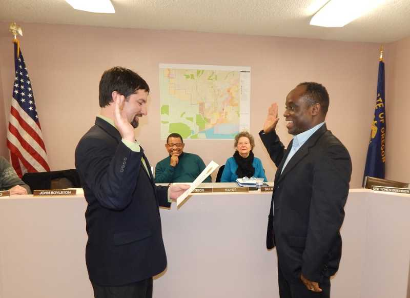 BARBARA SHERMAN - City Manager Mike Weston (left) reads the oath of office that is repeated by Smart Ocholi, who won his own four-year term on the King City Ciy Council in November after being appointed to the council last year.