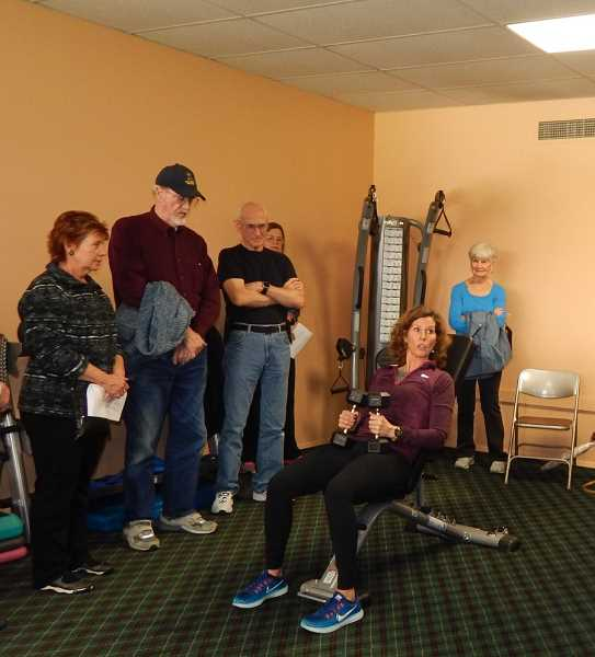 BARBARA SHERMAN - Summerfield residents watch professional trainer Connie Bear of Club Sport demonstrate how to use the new equipment Dec. 3.