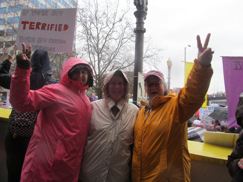PHOTO BY ELLEN SPITALERI - Showing solidarity before the start of the womens march were, left to right, Trisha Michael, Peg Ortner and Susie Pierce. They appreciated the positive energy of the event, in spite of the driving rain.