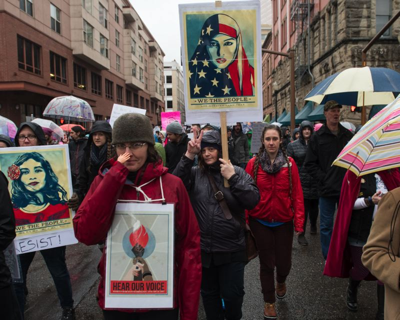 OUTLOOK PHOTO: JOSH KULLA - Portland Women's March protesters display creative and colorful banners and signs as they make their way along city streets.